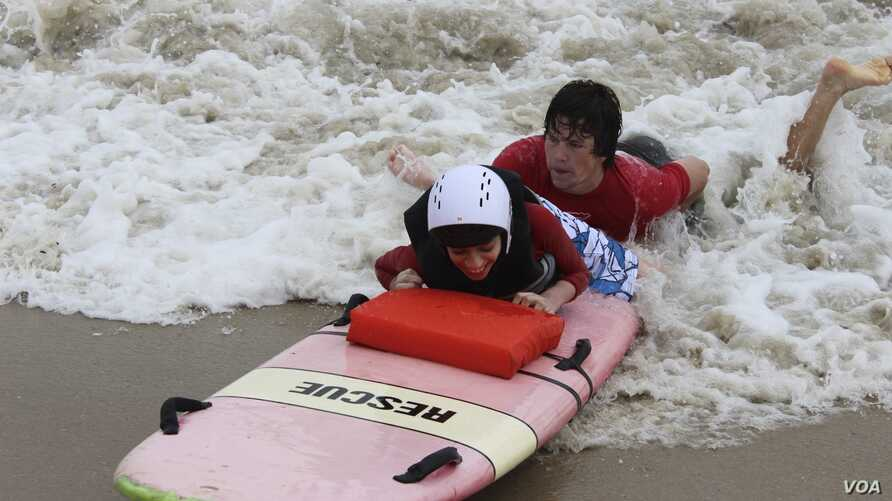 Austin Bramson takes a ride on a surfboard with the help of a Best Day at the Beach volunteer. (VOA/D. Gruenbaum)