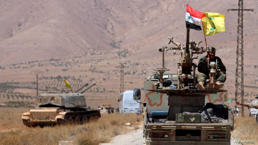 Hezbollah and Syrian flags flutter on a military vehicle in Western Qalamoun, Syria, Aug, 28, 2017.
