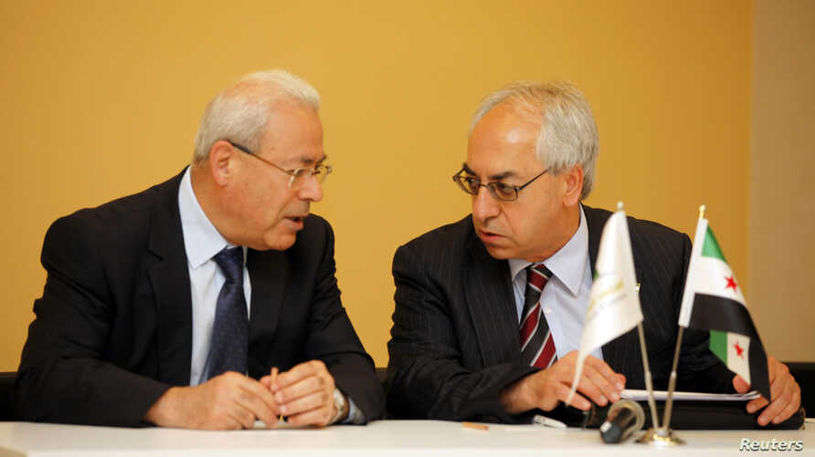 The new president of the Syrian National Council Abdelbasset Sieda (R) talks with former President Burhan Ghalioun before a news conference in Istanbul, June 10, 2012.