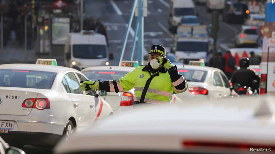 Due to air pollution in Madrid, a traffic policeman wears a mask while directing traffic, Dec. 29, 2016.