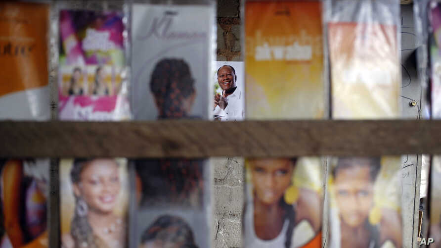 A poster of incumbent President Alassane Ouattara, center rear, is seen at a local hair dressing salon in Abidjan, Ivory Coast, Oct. 21, 2015.
