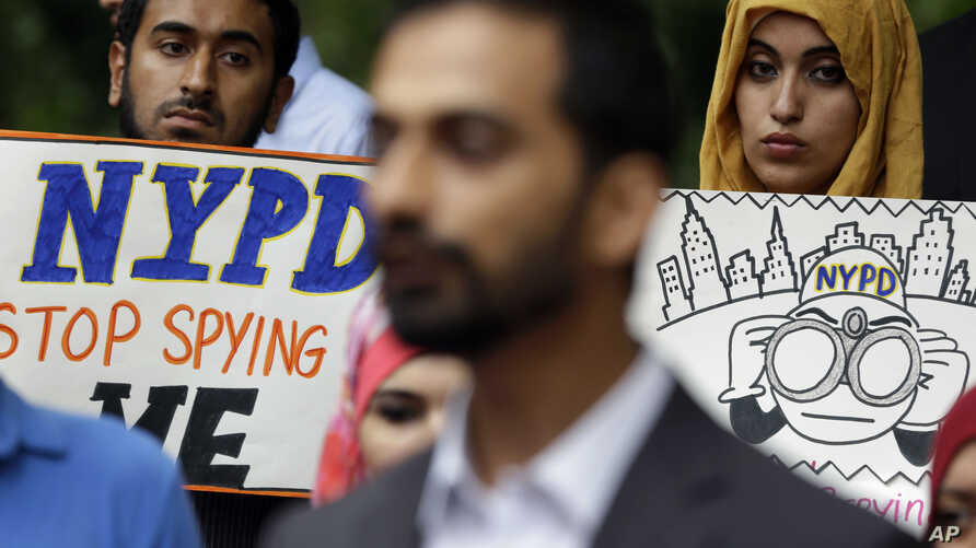 FILE - People hold signs while attending a rally to protest New York Police Department surveillance tactics near police headquarters in New York, Aug. 28, 2013.