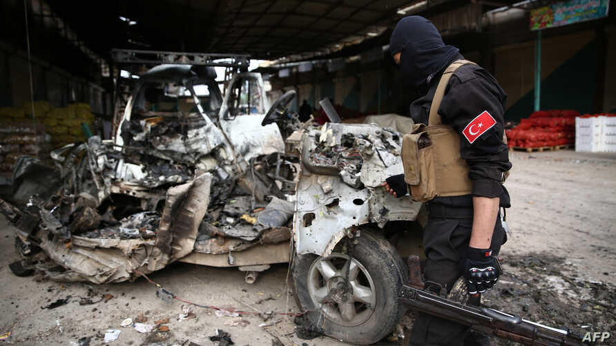 FILE - A Turkey-backed Syrian fighetr inspects the remains of a car that reportedly exploded in a market in the northern Syrian city of Afrin, killing and wounding several people, Dec. 16, 2018.