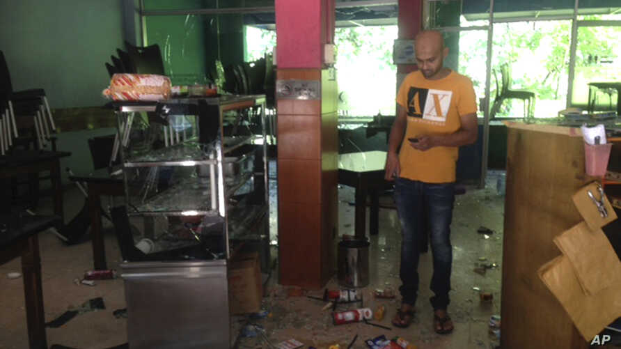 Mohamed Ramzeen makes a call from his mobile phone standing in his vandalized small restaurant in Pilimathalawa, Sri Lanka, Thursday, March 8, 2018.