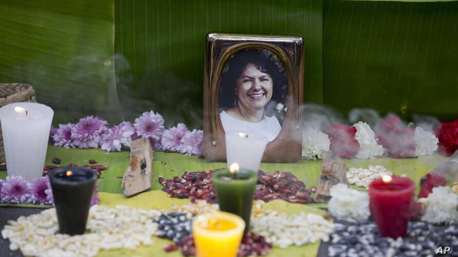 FILE - In this June 15, 2016, file photo, a picture of Berta Caceres sits on an altar in her honor during a demonstration outside Honduras' embassy in Mexico City.
