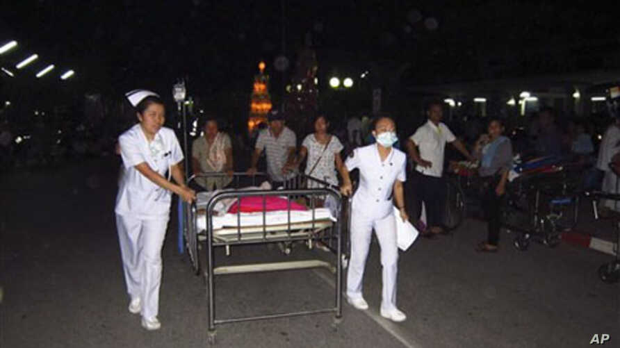Nurses help pushing a patient's bed as they are evacuated from a hospital building following an earthquake at Chiang Rai hospital in Chiang Rai province, northern Thailand, March 24, 2011