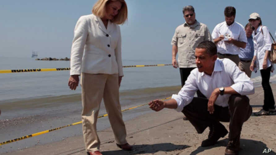 President Barack Obama and Lafourche Parish President Charlotte Randolf, left, inspect a tar ball as they look at the effect the BP oil spill is having on Fourchon Beach in Port Fourchon, Louisiana, May 28, 2010. (Official White House Photo by Chuck