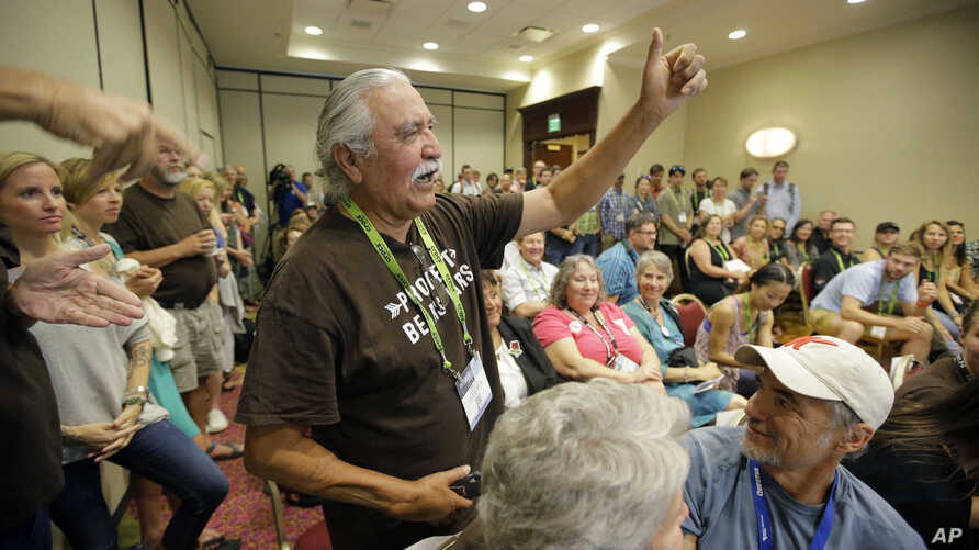 FILE - Willie Grayeyes, of the Utah Dine Bikeyah, raises his hand as he is recognized during a news conference, in Salt Lake City, Aug. 4, 2016. Navajo Nation leaders are protesting a Utah county's investigation into a Navajo candidate's residency, s