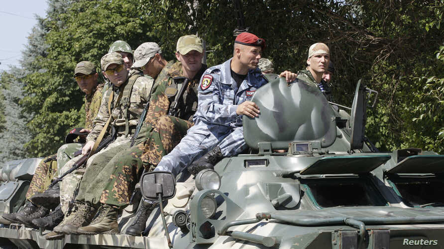 FILE - Members of a special military unit of the separatist self-proclaimed Lugansk People's Republic drive an armored vehicle as they take part in a drill in Luhansk, Ukraine, July 10, 2018.