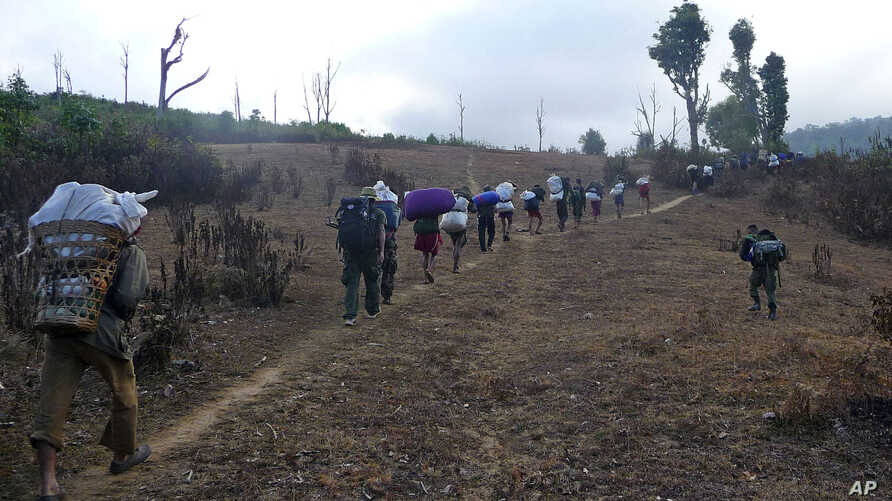 In this Friday, Jan. 8, 2010 picture released by the Free Burma Rangers, Karen villagers carrying relief supplies walk on a path as they flee Burmese soldiers in Karen State.