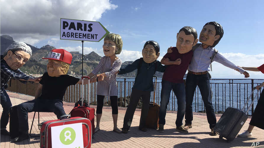 Oxfam activists wearing masks of the leaders of the G-7 summit (from left) Italian Premier Paolo Gentiloni, US President Donald Trump, German Chancellor Angela Merkel, Japanese Prime Minister Shinzo Abe, French President Emmanuel Macron and Canadian