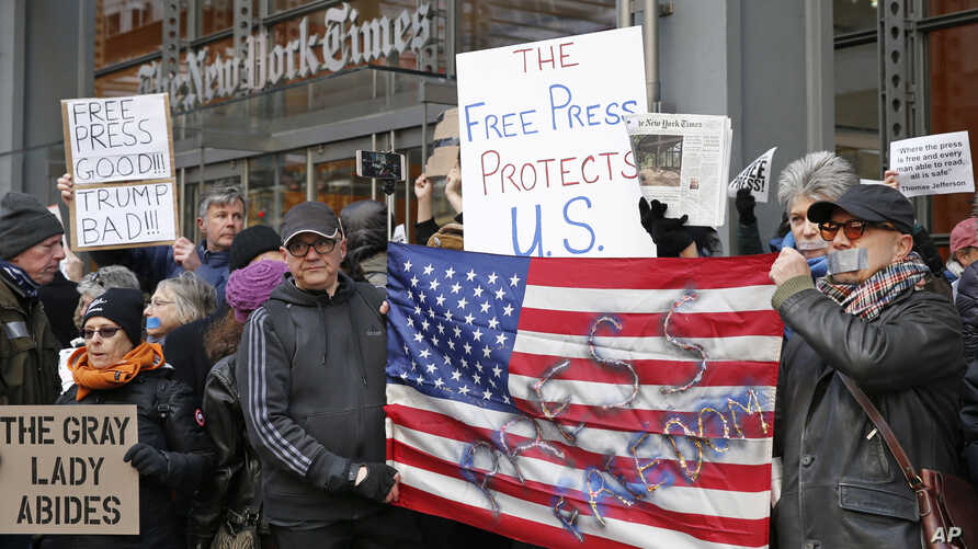 FILE - Demonstrators stand with U.S. flags and signs in a show of solidarity with the press in front of The New York Times building in New York, Feb. 26, 2017.