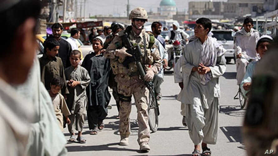 Canadian soldiers of Task Force Kandahar walk with locals down a street as they conduct a foot patrol in Kandahar city (File)