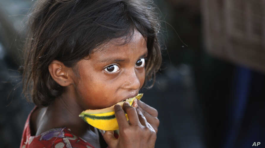 A child laborer eats a piece of a muskmelon on the World Day against Child Labor on the outskirts of Jammu, India, June 12, 2015.