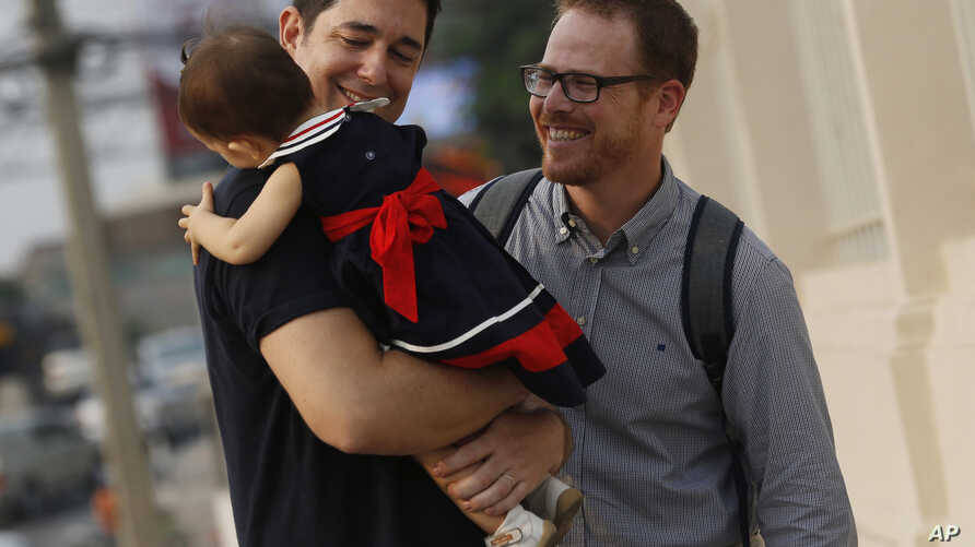 American Gordon Lake, left, and Manuel Santos, right, walk with their baby Carmen, center, at the Central Juvenile and Family Court in Bangkok, Thailand, Wednesday, March 23, 2016.