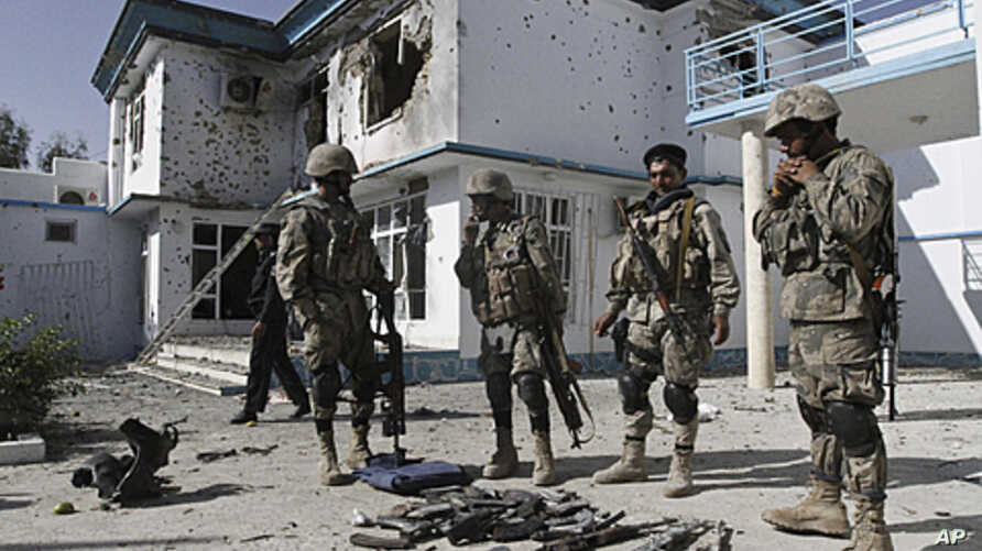 Afghan policemen display confiscated arms belonging to insurgents after a suicide bomb attack followed by a gun battle between the insurgents and U.S. and Afghan forces at a building used by the Office of the United Nations High Commissioner for Refu