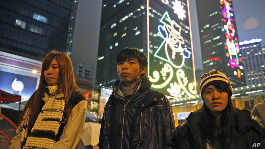 Three students, from right, Prince Wong, Joshua Wong and Isabella Lo walk at the occupied area outside government headquarters during their hunger strike in Hong Kong Wednesday, Dec.3, 2014.