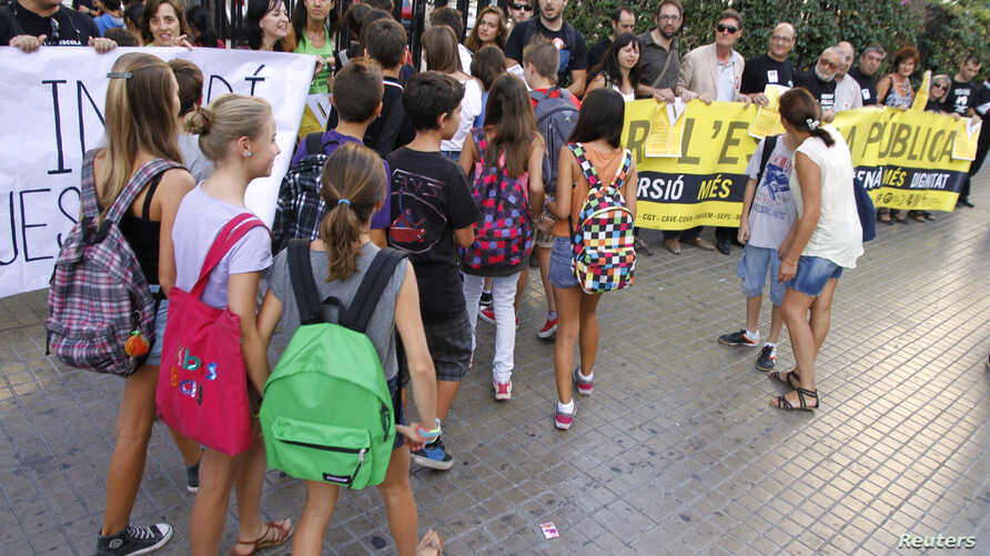 Students enter Luis Vives secondary school as teachers protest against cuts in public education, in Valencia, Spain, September 14, 2012. The yellow banner reads: 'For public school.'