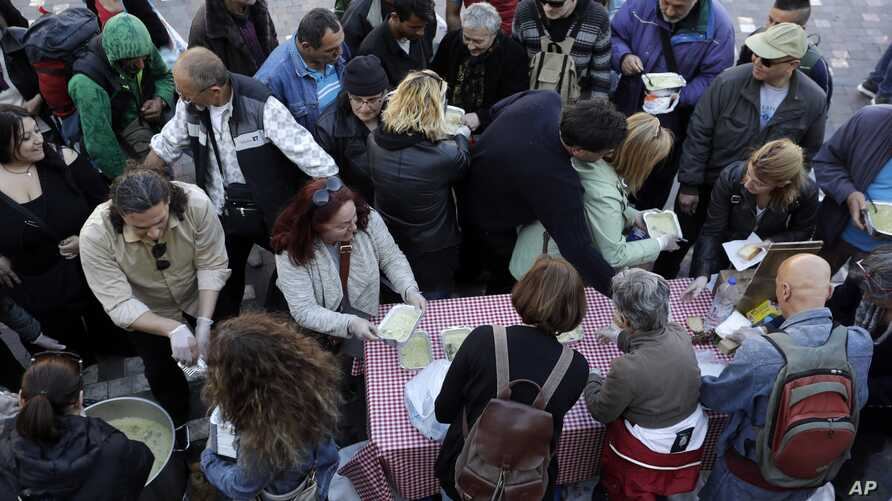 Soup kitchen volunteers hand out free food in Central Athens, where there is high unemployment and a steady decline of living standards for most Greeks for seven consecutive years