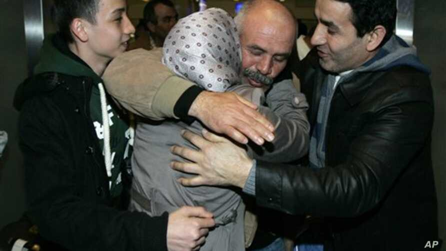 A Turkish man, second from right, greets family members after arriving in Turkey from Libya February 22, 2011.