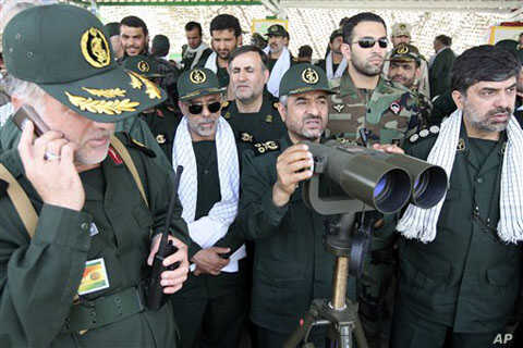 In this photo released by the semi-official Iranian Fars News Agency, Iranian Revolutionary Guard commander Mohammad Ali Jafari, center, monitors maneuvers by the Iranian Revolutionary Guard, near the Strait of Hormuz, 24 Apr 2010