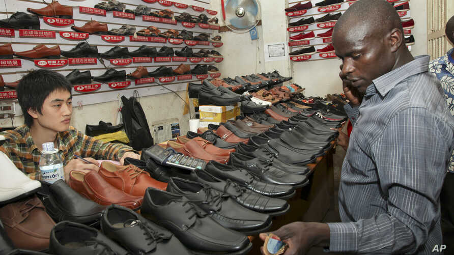 FILE - A Chinese shoe-seller, who declined to give his name, watches as a customer inspects his wares, at a shoe shop in Kampala, Uganda, June 8, 2015. Local merchants have been protesting the presence of Chinese traders, claiming unfair competition.