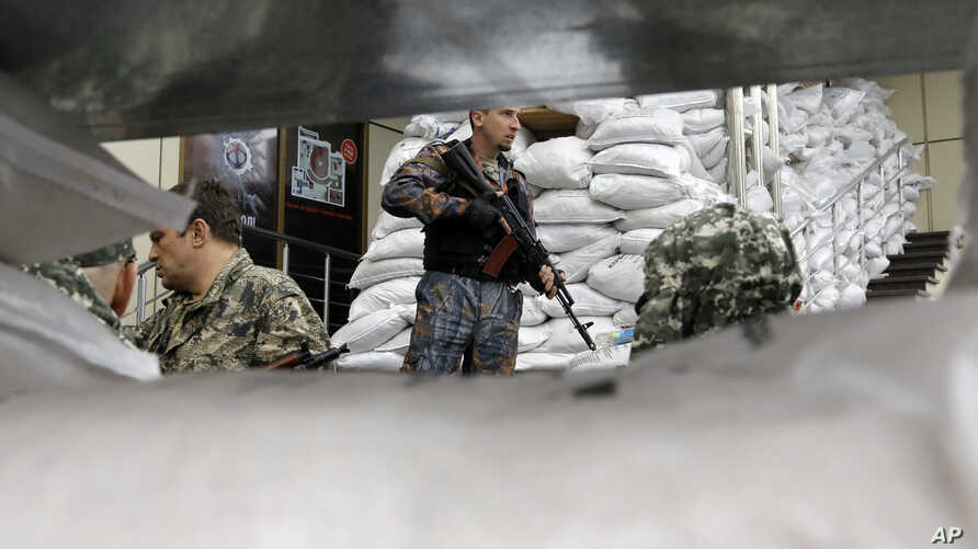 Pro-Russian fighters guard their military unit in the city of Donetsk, eastern Ukraine, June 27, 2014.