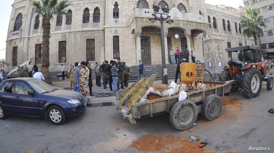 People gather around the scene of a bomb explosion in front of of al-Hijaz train station in central Damascus, Nov. 6, 2013, in this handout picture released by SANA.