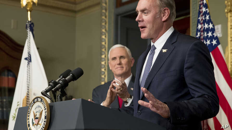 Vice President Mike Pence applauds as newly sworn in Interior Secretary Ryan Zinke addresses the crowd, March 1, 2017, in the Eisenhower Executive Office Building in Washington.