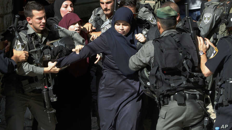 Israeli border police officers scuffle with Palestinian women in the Old City of Jerusalem on Sunday, July 26, 2015.
