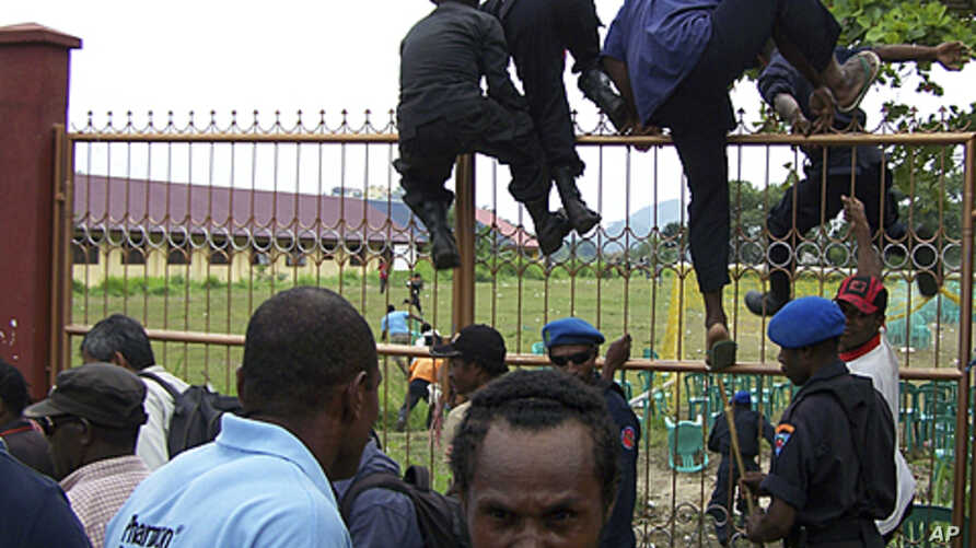 Papuanese who attended the Third Papuan People Congress climb a fence after police and troops dispersed the crowd at the event in Abepura in Indonesia's Papua province, October 19, 2011.