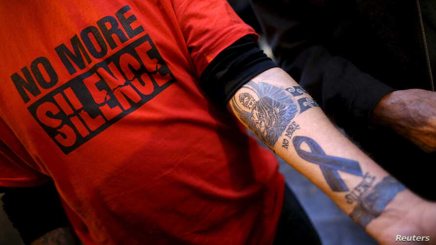 "FILE - Paul Levely, a child sex abuse victim, wears a T-shirt that says ""no more silence"" and shows a tattoo on his arm in Rome, Italy, Feb. 28, 2016. The Catholic Church in Australia is rejecting laws forcing priests to report confessions of child a..."