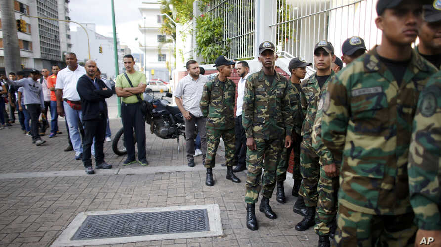 Venezuelan Bolivarian Army soldiers lineup to vote for the constitutional assembly outside of a poll station in Caracas, Venezuela, July 30, 2017.