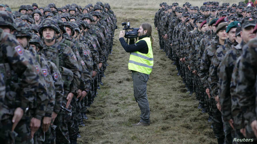 FILE - A cameraman films soldiers after a military exercise in Pocek, Slovenia.