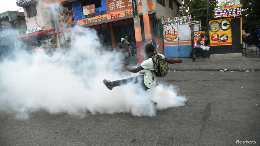 A demonstrator kicks a teargas canister during clashes with Haitian police in Port-au-Prince, Feb. 15, 2019, on the ninth day of protests against Haitian President Jovenel Moise.