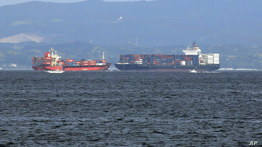FILE - In this Saturday, June 17, 2017, photo, the damaged Philippine-registered container ship ACX Crystal, right, cruises past another container ship off Yokosuka, south of Tokyo, after colliding with the USS Fitzgerald off Japan earlier in the day