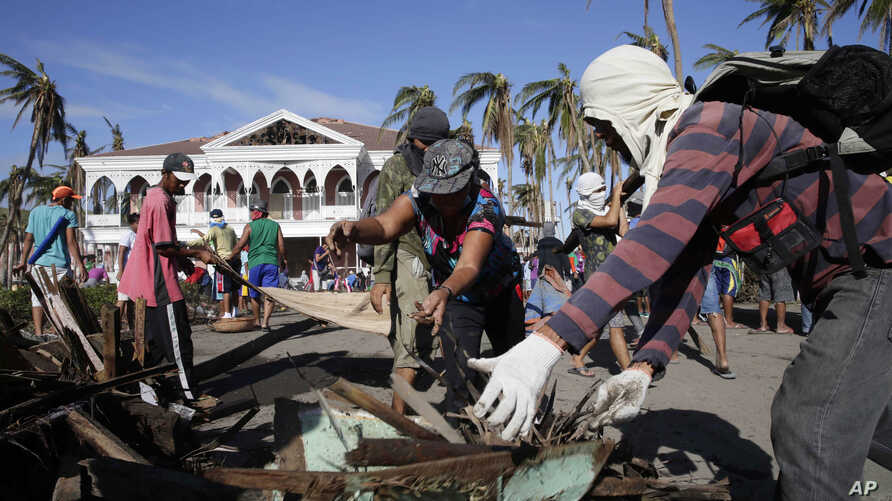 Typhoon survivors and volunteers begin a massive clean up in typhoon-ravaged Tacloban city, Leyte province in central Philippines, Nov. 25, 2013.