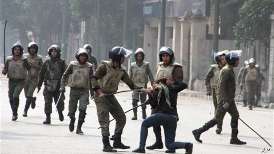 Egyptian army soldiers arrest a woman protester during clashes with military police near Cairo's downtown Tahrir Square,  Egypt Friday, Dec. 16, 2011.