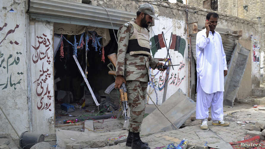 An army soldier stands with a police officer in front of a damaged Pakistan People's Party (PPP) election campaign office after a bomb blast, in Quetta, May 10, 2013.