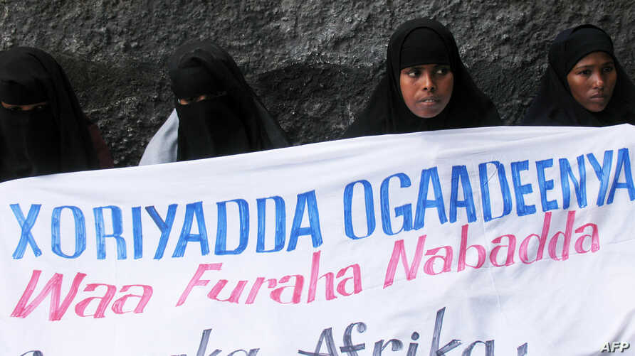 "FILE - Ogaden National Liberation Front activists hold a banner in Mogadishu that reads, ""The Ogaden freedom is the key to peace in the Horn of Africa,"" during a ceremony that marked the organization's 22nd anniversary in Somalia, Aug. 15, 2006."
