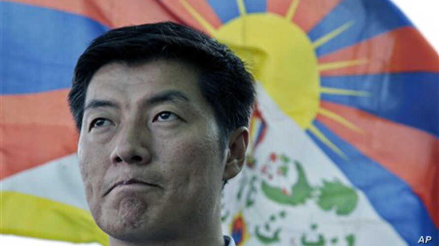 In this March 20, 2011 file photo, newly-elected Tibetan prime minister Lobsang Sangay talks to the Associated Press with a Tibetan flag in the background in Dharmsala, India.