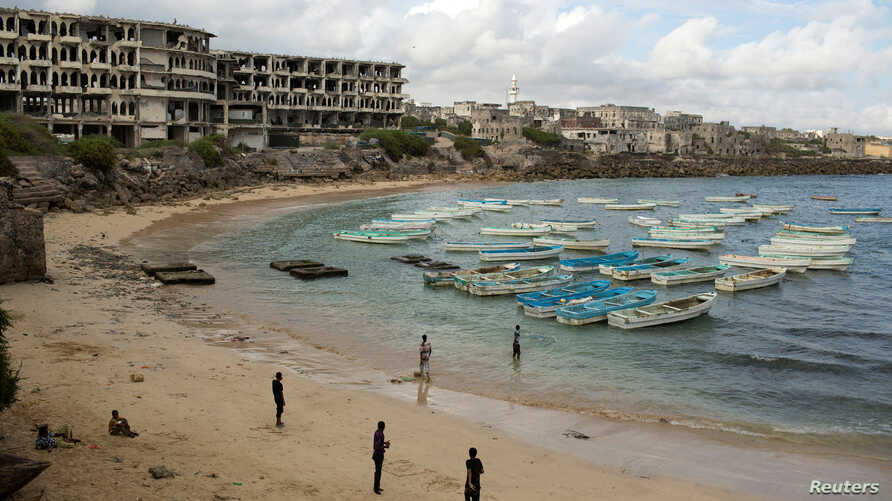 FILE - People stand and walk on a beach in the old port of Mogadishu, Somalia, Nov. 13, 2013. Global watchdog Transparency International said  Wednesday its latest annual Corruption Perceptions Index report showed pervasive public-sector corruption a