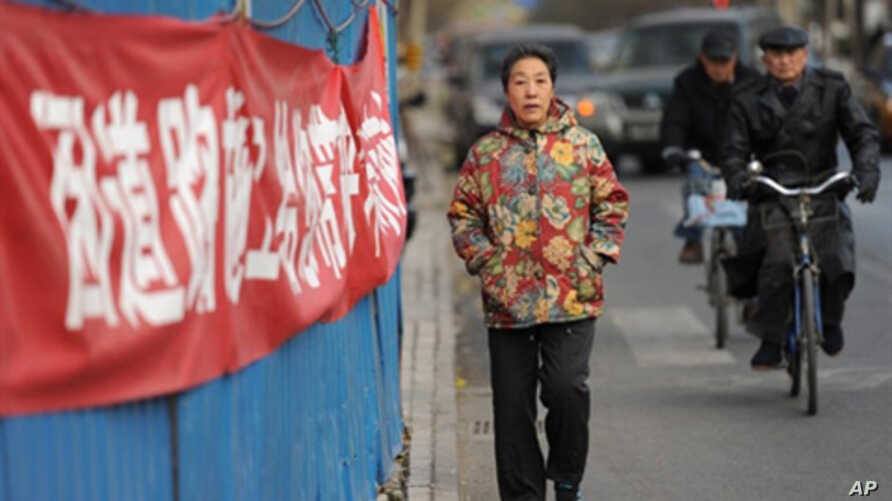 A woman walks outside the housing compound of jailed Chinese dissident Liu Xiaobo, the 2010 Nobel Peace Prize winner, in Beijing, Dec. 8, 2010. Liu is to be honored on Dec. 10 at the Nobel awards ceremony in Oslo.