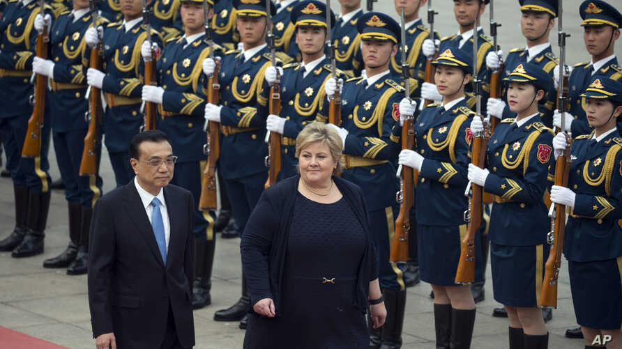 Norwegian Prime Minister Erna Solberg, second from left, walks with Chinese Premier Li Keqiang during a welcome ceremony outside the Great Hall of the People in Beijing, China, April 7, 2017.