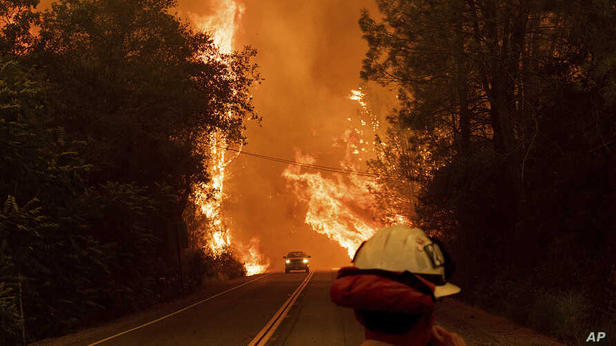 A car passes through flames on Highway 299 as the Carr Fire burns through Shasta, Calif., July 26, 2018. Fueled by high temperatures, wind and low humidity, the blaze destroyed more than 500 structures and has killed two firefighters.