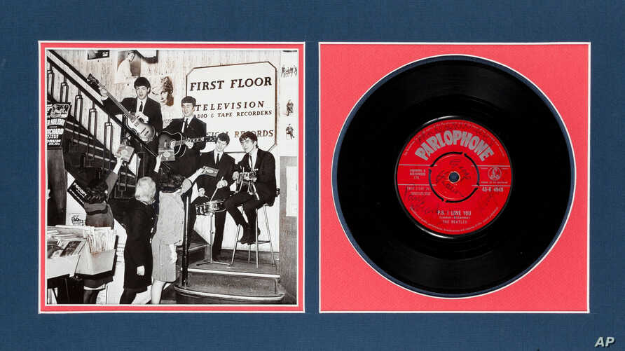 """This undated photo provided by Heritage Auctions from an upcoming Beatles collection sale shows a signed copy of their first hit, """"Love Me Do,"""" which will be auctioned in New York on Sept. 19."""
