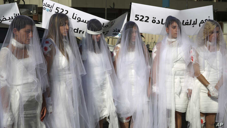 FILE - Lebanese women, dressed as brides in white wedding dresses stained with fake blood and bandaging their eyes, knees and hands stand in front of the government building in downtown Beirut, Lebanon, Dec. 6, 2016.