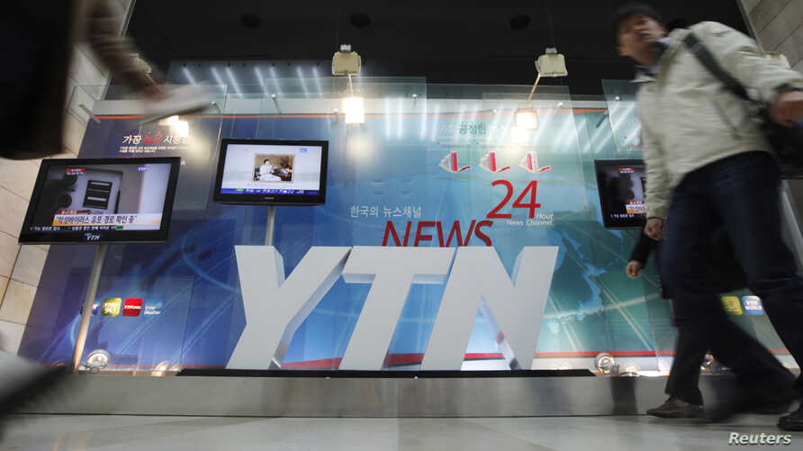 A TV crew walks by at the main office of television network YTN, in Seoul, March 20, 2013.