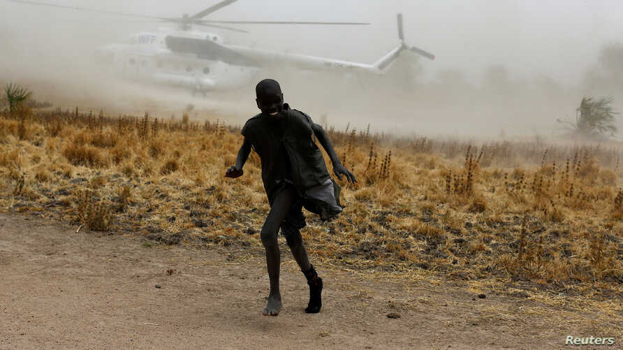 A boy moves away as a United Nations World Food Programme (WFP) helicopter lands in Rubkuai village, Unity State, northern South Sudan, February 18, 2017.
