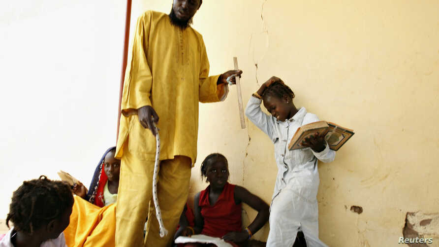 FILE - A girl (R) winces in pain after being hit on the head with a stick by her instructor (C) at a Daraa, or Koranic school, in Pikine on the outskirts of  Dakar, May 7, 2008.